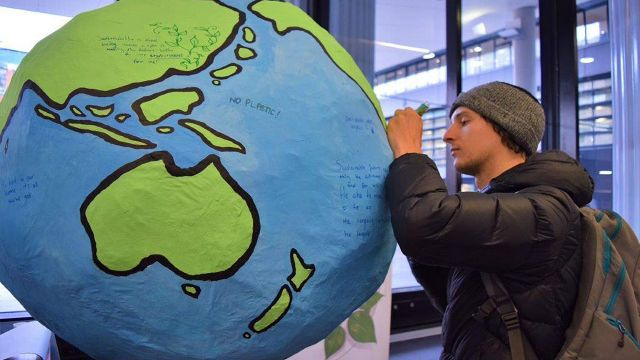 Student writes sustainability goals on paper globe