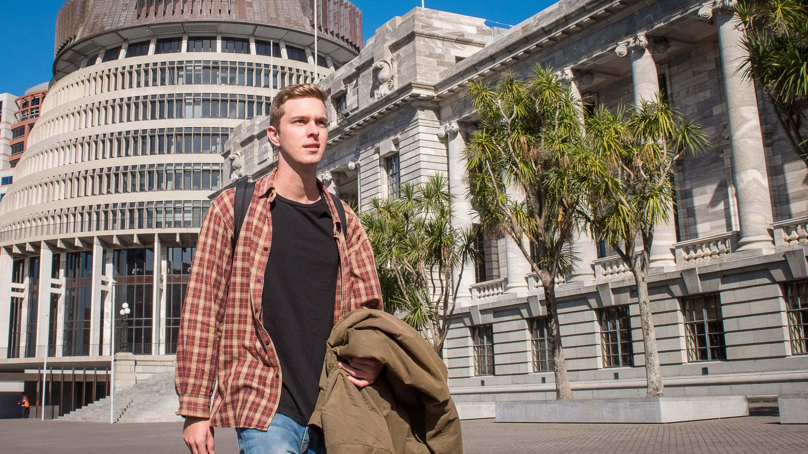 A young man dressed in a plaid shirt, black top, and blue jeans walks past the complex of New Zealand Parliament.