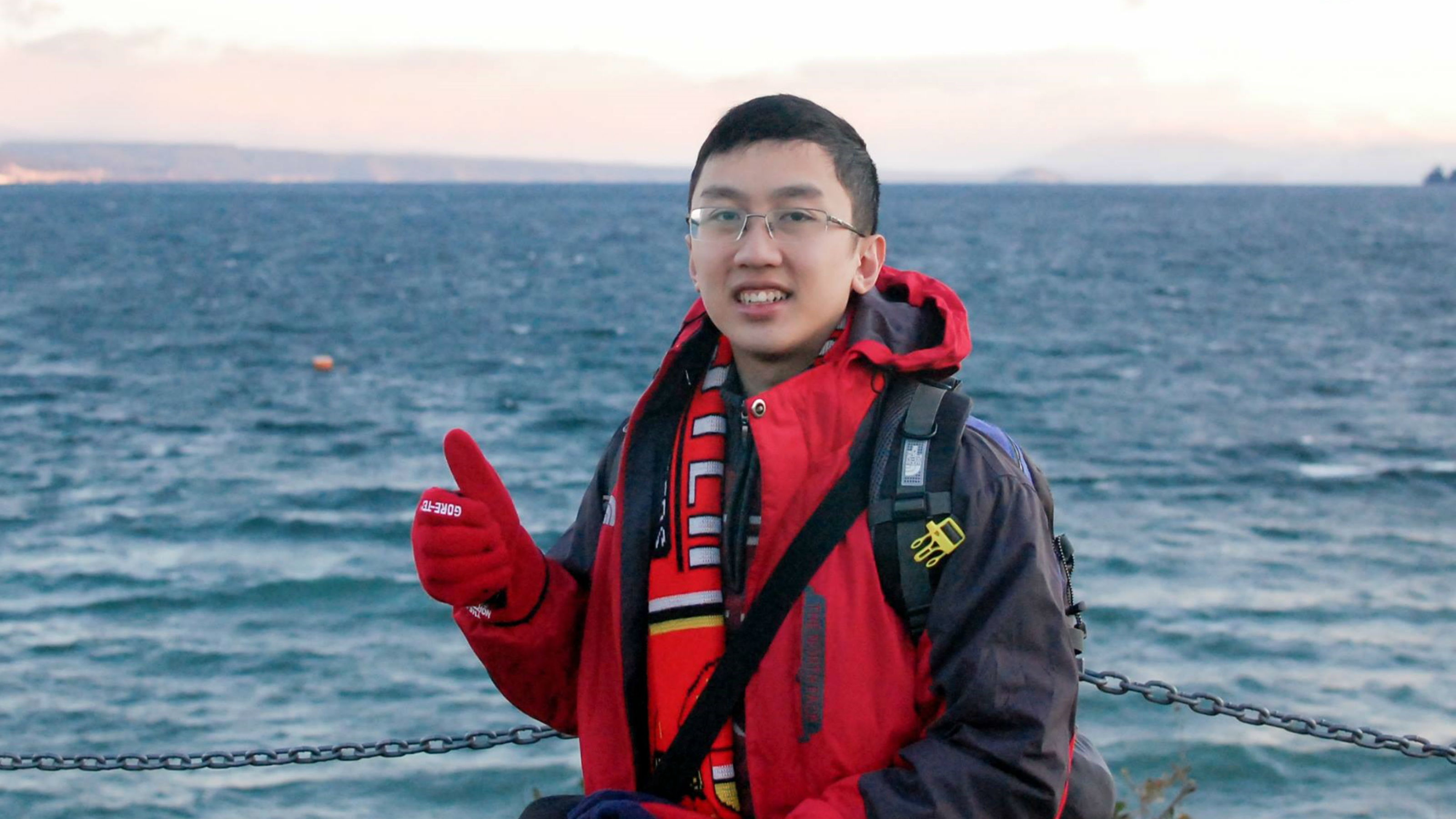 Quan Trong Nguyen in a big red jacket gives a gloved thumbs-up before a body of blue water and coastline in the offing.