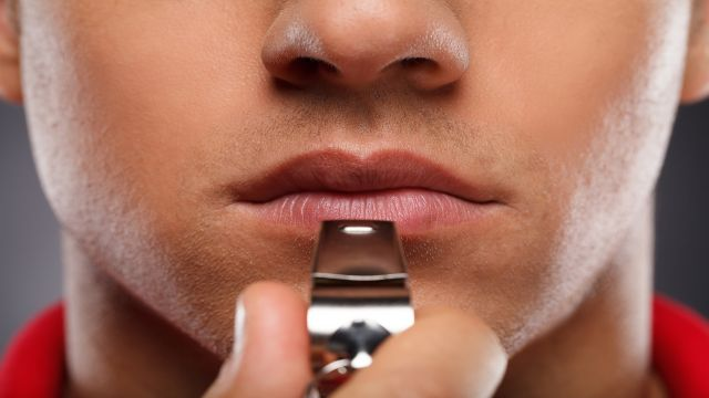 A silver whistle ready at the lips of a man.
