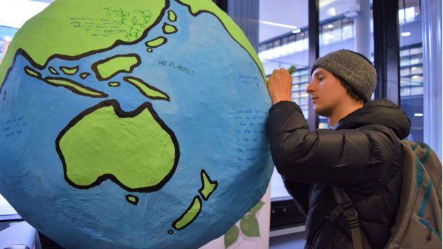 Student writing on a large paper mache globe.