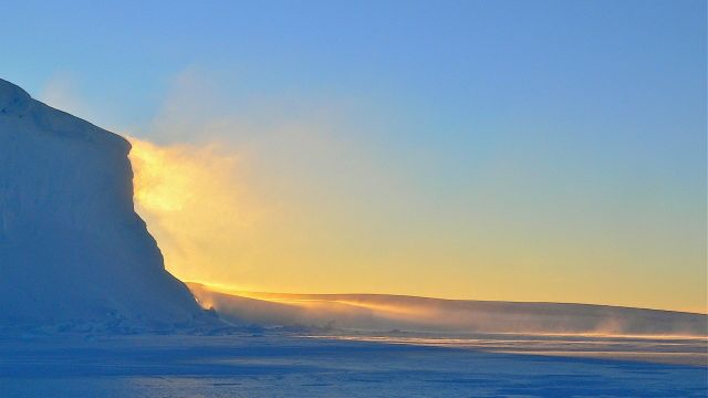 Golden curl of snow blowing off of an iceberg.