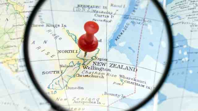 New Zealand pin pointed on a map of the world.