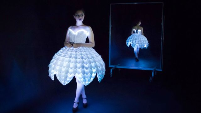 The dress 'Ester' is white with LED lights underneath lighting it up/
