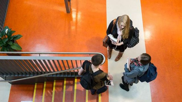 Birds-eye view of three students chatting in the atrium of the Architecture and Design schools at Te Aro campus