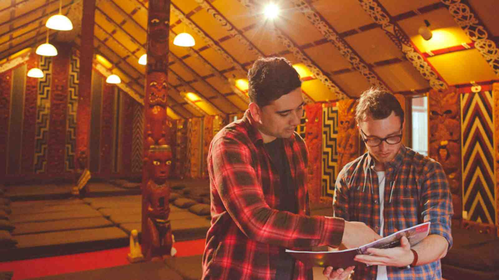 Two students standing in Victoria's Te Herenga Waka Marae and looking at a publication together.