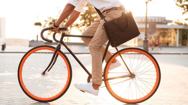 A man riding a bicycle with orange-lined tyres.