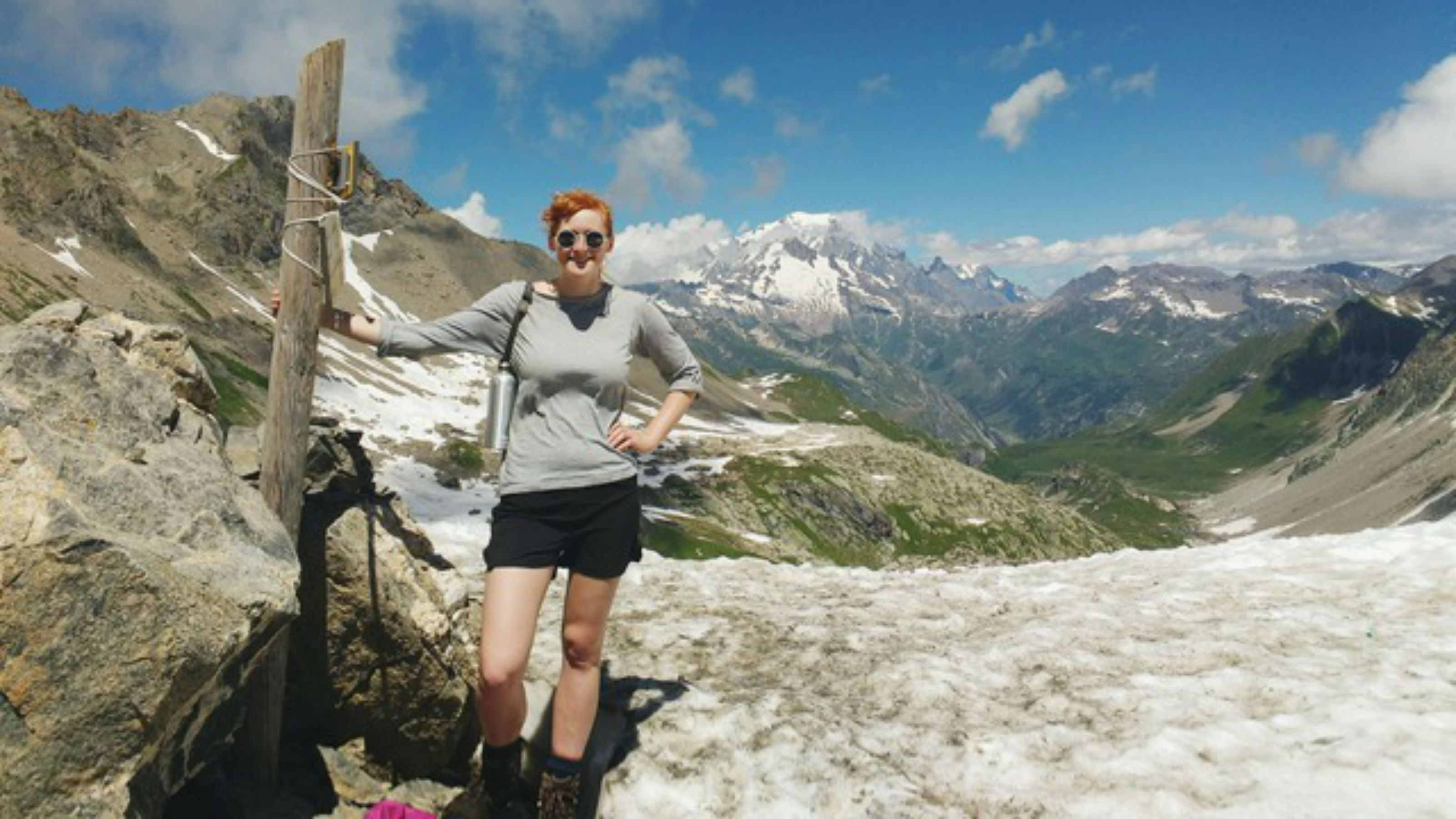 PhD candidate, Florence Isaacs stands next to a wooden box in the French Alps, with mountain scenery behind her