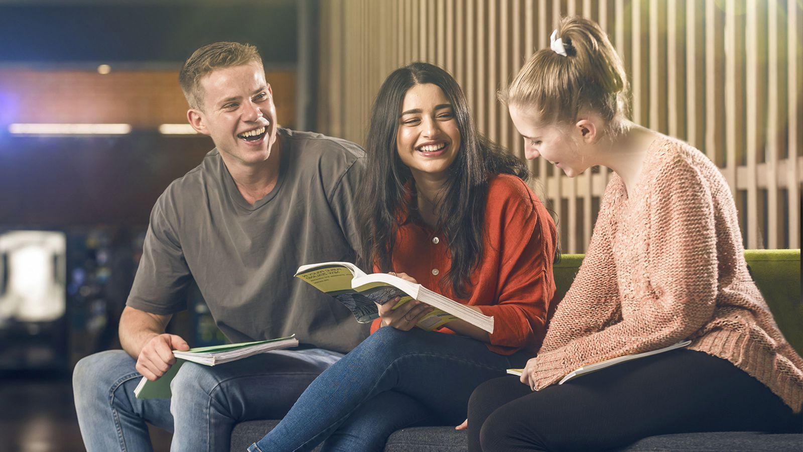 Three students sit on a couch and smile while studying a text book.