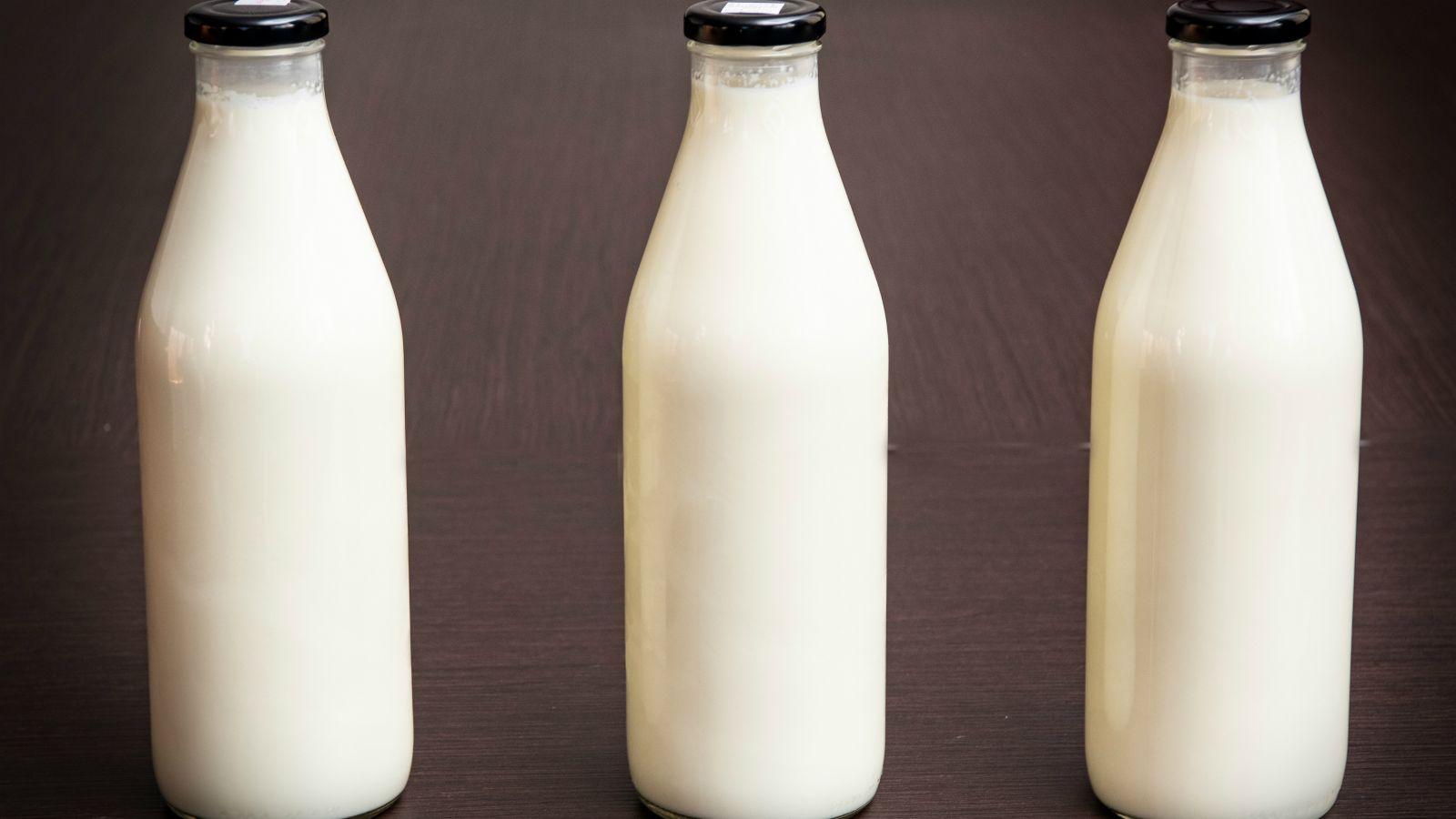 Three one litre full milk bottles