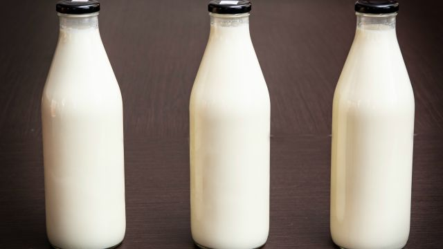 Three one litre full milk bottles