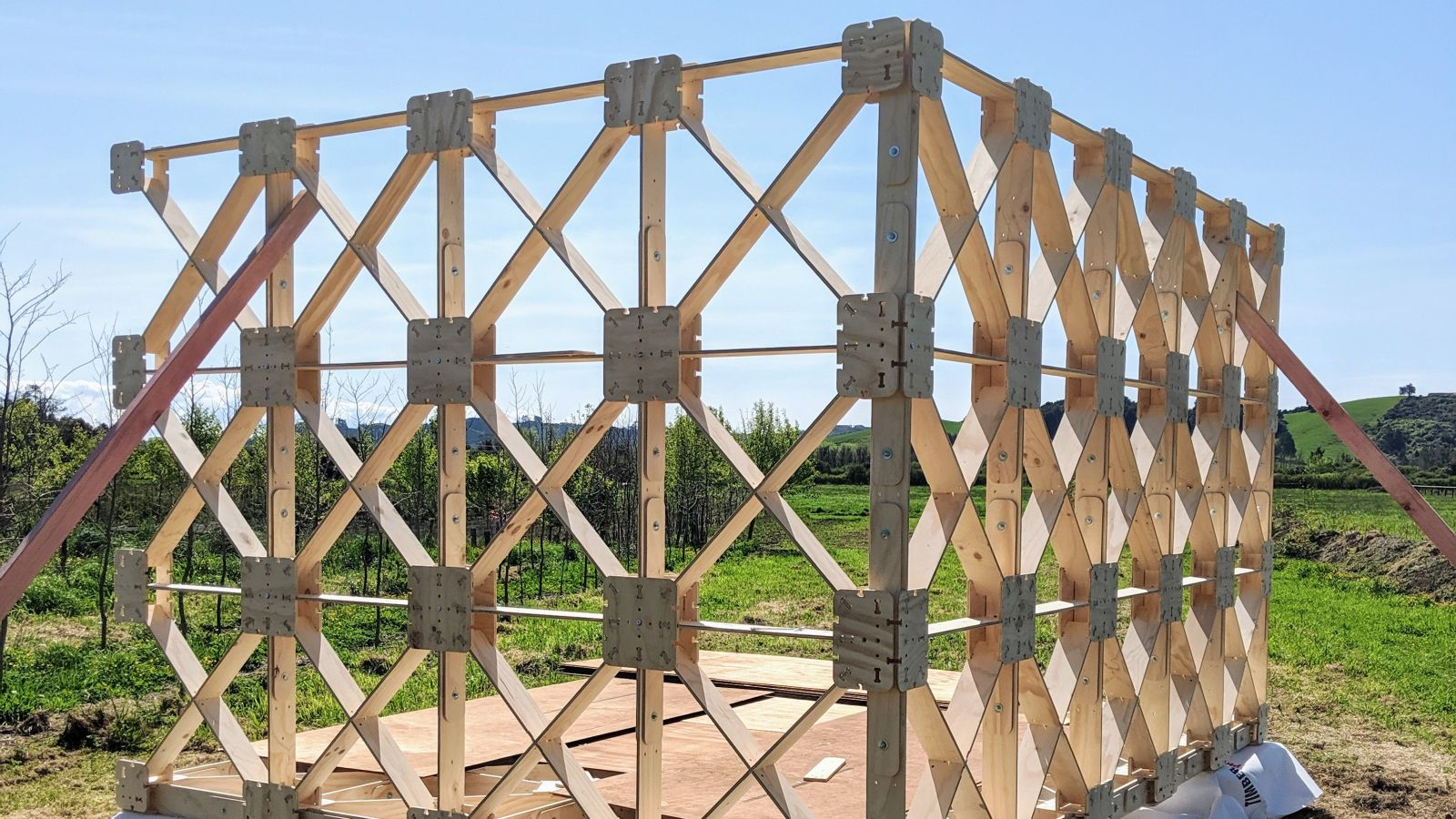 Ged Finch's xframe prototype being constructed. Two wooden panels of x shaped wood constructed in field