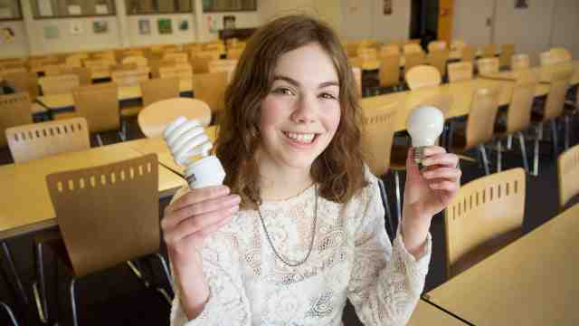 Bethany Paterson sits at a desk holding two lightbulbs