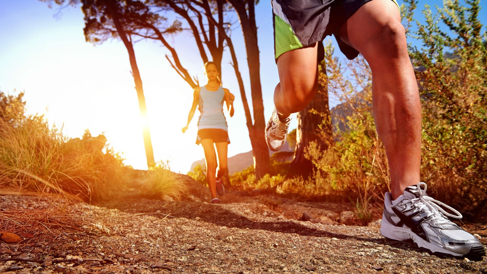 A man and a woman running through a forrest tree line on a sunny morning