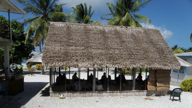 People sit in hut in Atafu Village