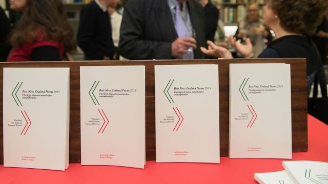 A view of four books with people talking in the background