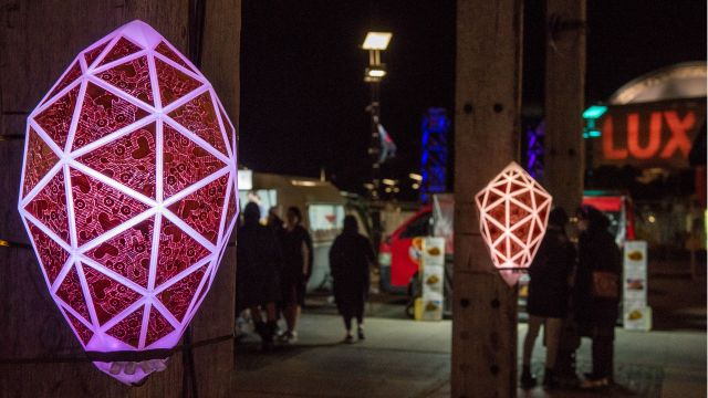 Geometric lights glow at night on wooden poles in the city.