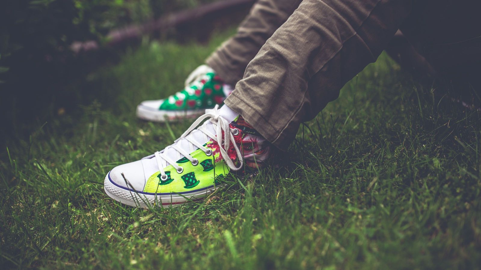 white and green sneakers worn by someone sitting with their feet on the lawn, close up of the feet