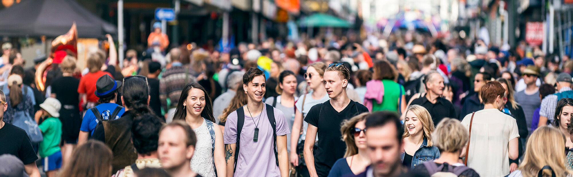 Smiling university students in the crowd at CubaDupa, a street festival in Wellington