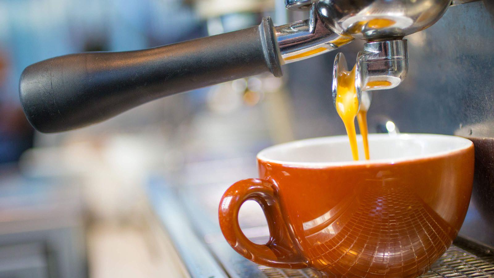 Espresso beginning to stream from a portafilter's snout into a red ceramic mug.