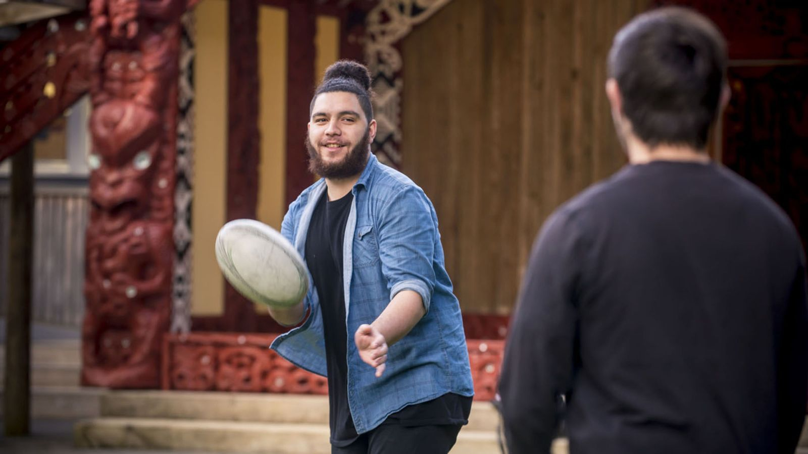 One young man passes a rugby ball to another on the grass outside a marae.