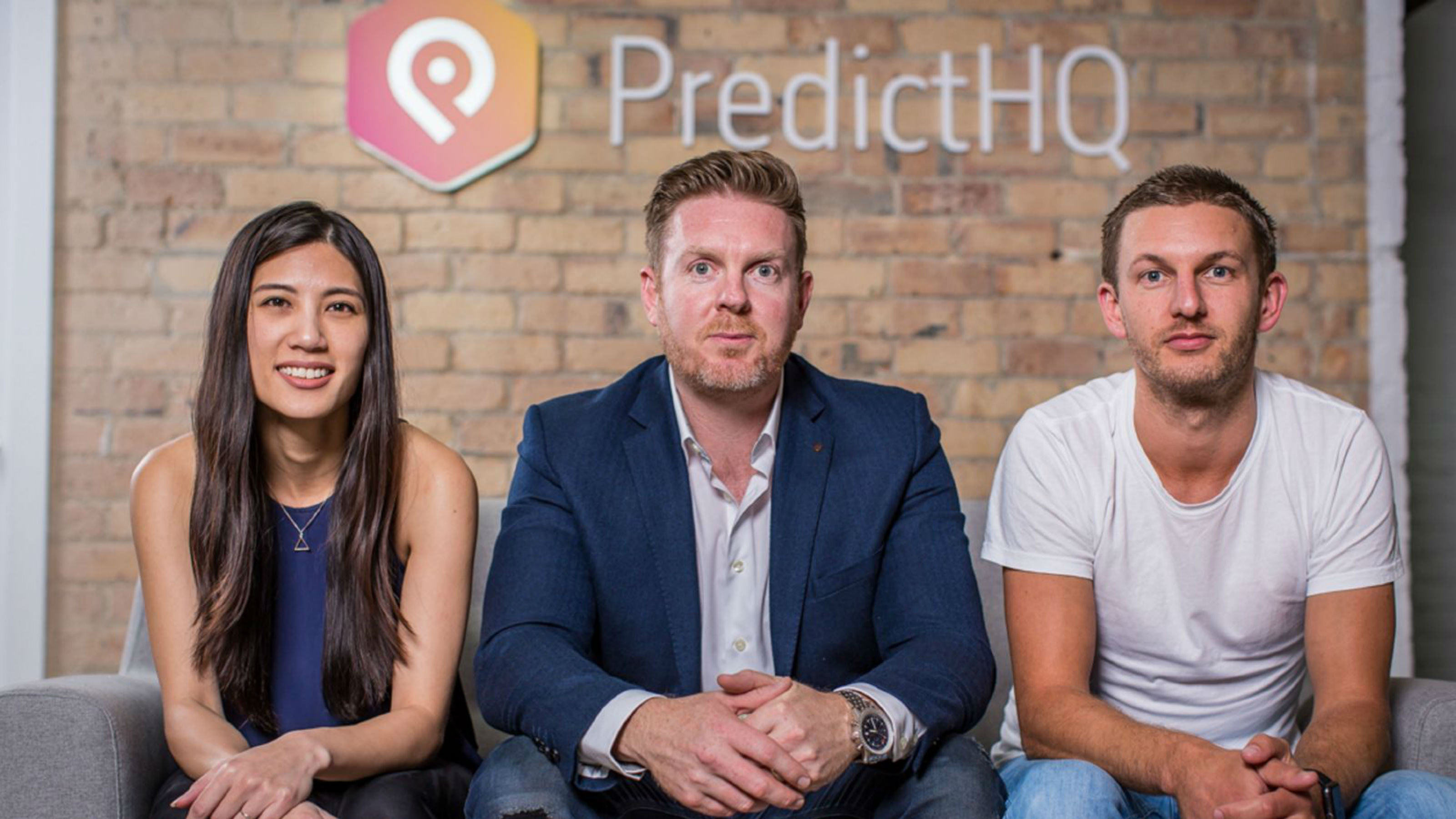 Yen Lim, Campbell Brown and Rob Kern sit next to each other on a sofa with a brick wall, company logo and words 'PredictHQ' behind them.