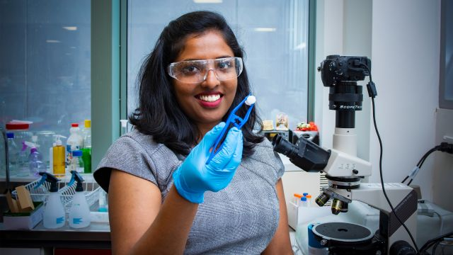 Dr Mima Kurian, wearing safety glasses and a blue lab glove, holds up a piece of paua with a pair of tweezers. She stands next to a microscope. Behind her is a bench with lab equipment and windows.