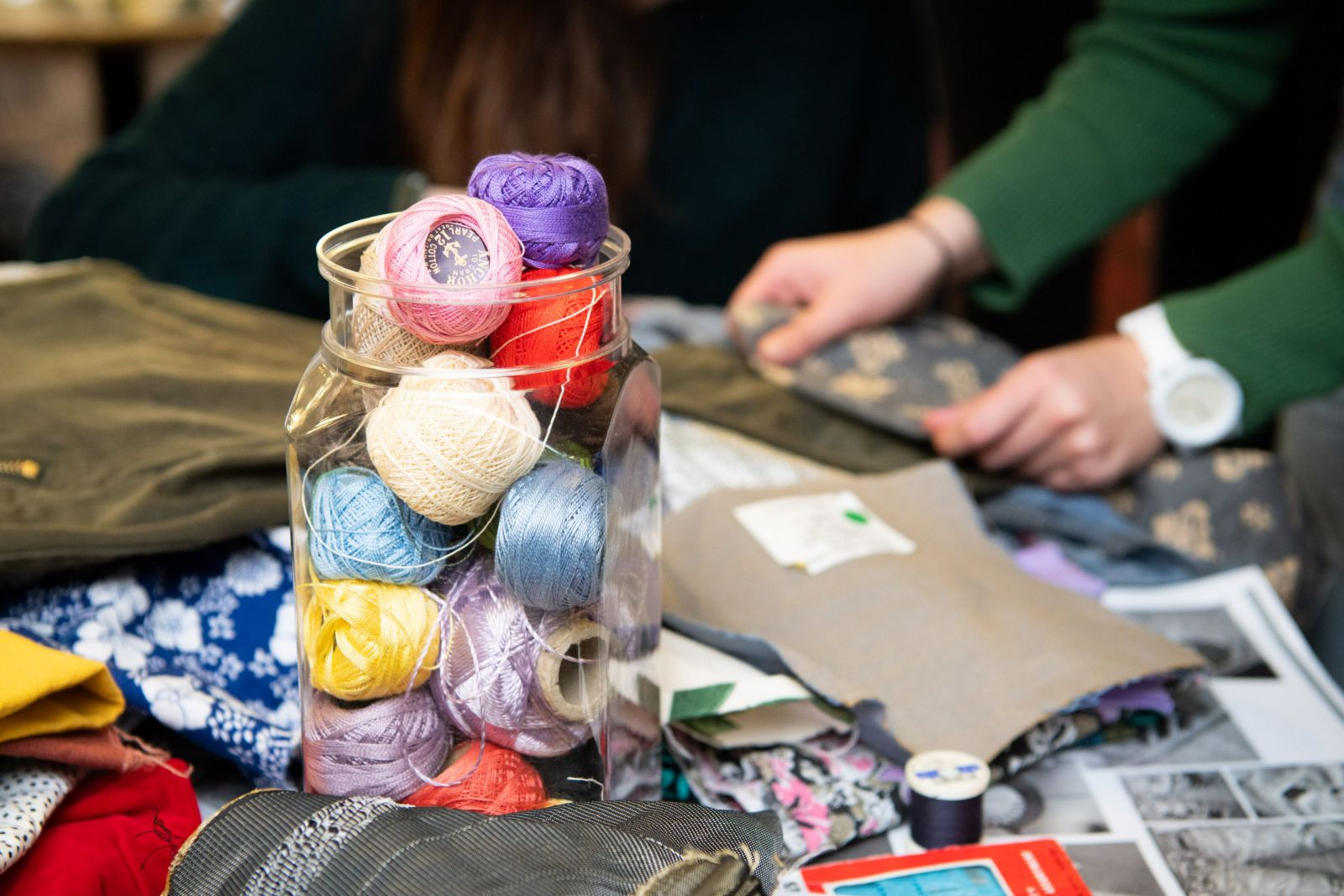Large jar of coloured thread and sewing materials.