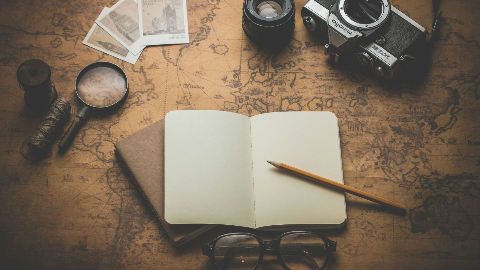 A notebook, pencil, magnifying glass, spectacles, camera and polaroids on a background of an old school world map.