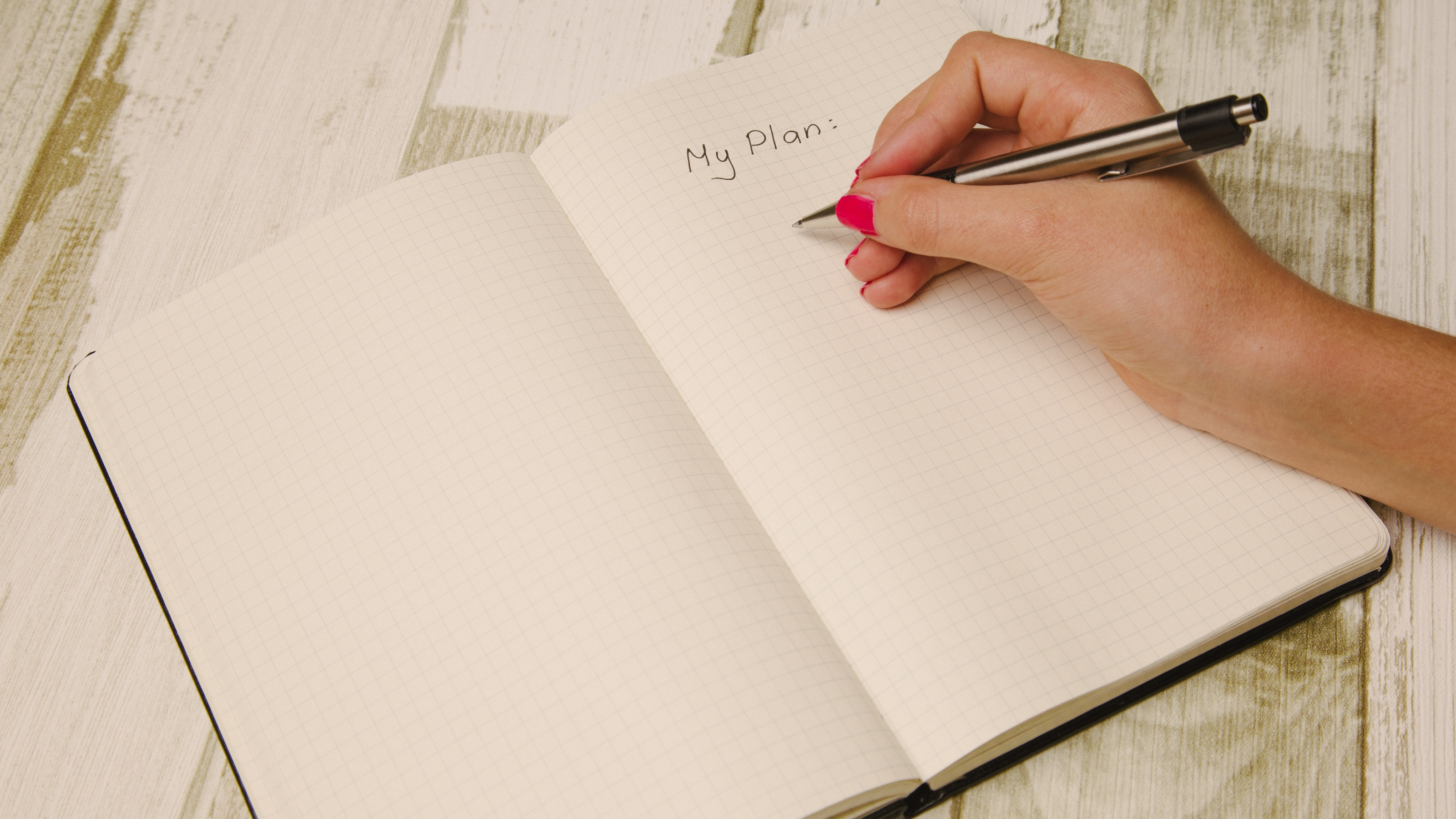 A hand writing 'My Plan' in a blank book.