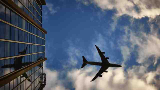 A plane high in a blue and cloudy sky, reflected in a sky scraper.