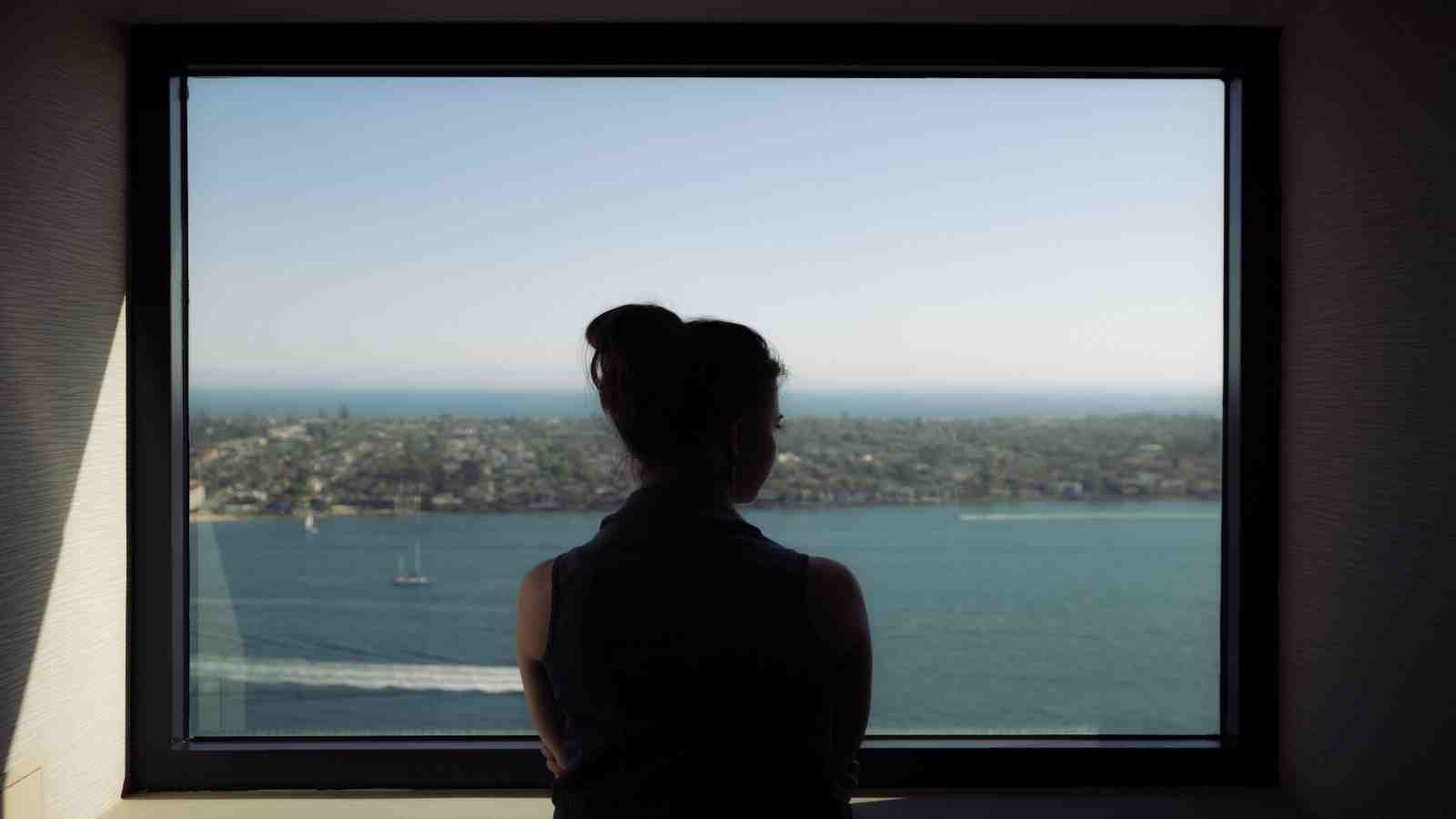 silhouette of woman looking out of window frame at lovely view