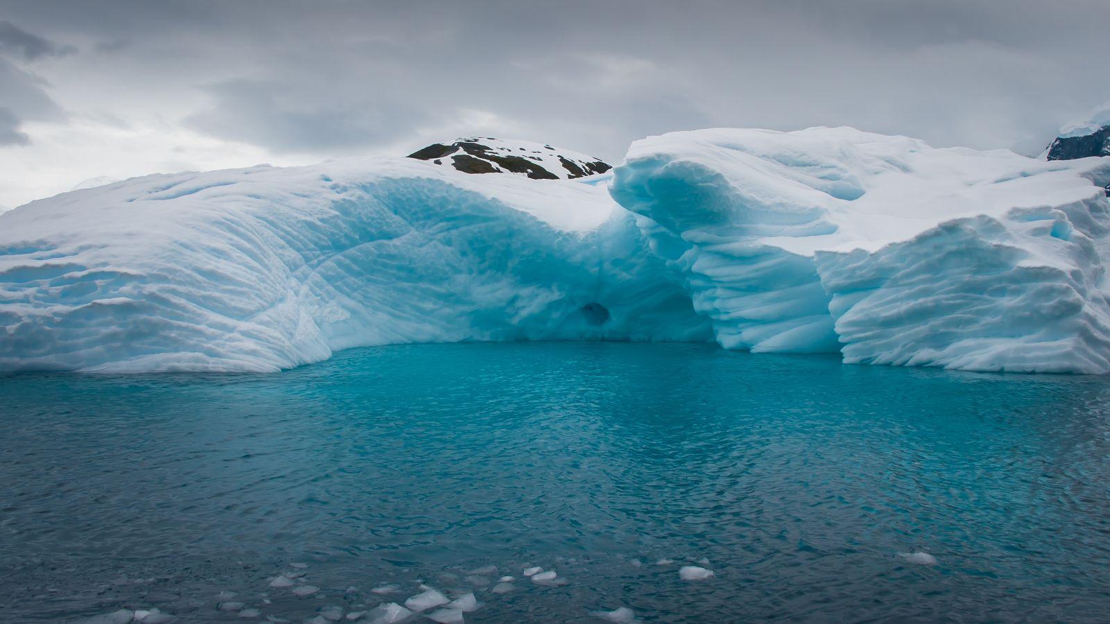 Landscape of an iceberg in a deep blue antarctic sea
