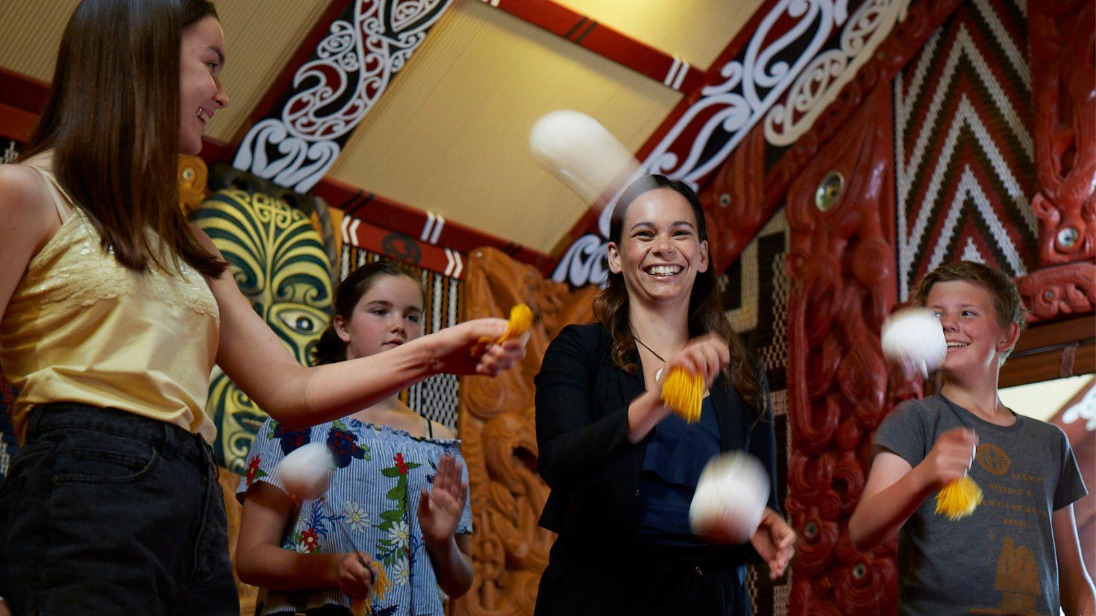 Teacher education students and school children swinging poi at Te Herenga Waka Marae, Victoria University's Kelburn campus.