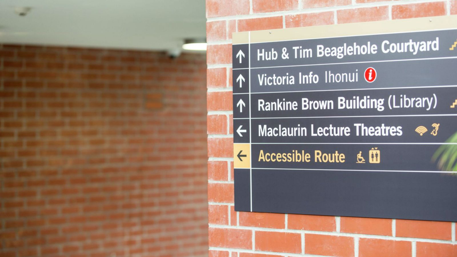 A black sign on a brick wall that shows where an accessible route is located.