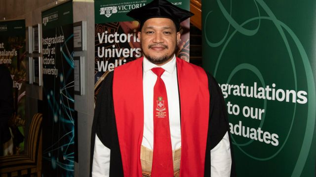 PhD graduate Taitusi Taufa, wearing a graduation cap and gowns, stands in front of a row of Victoria University of Wellington banners