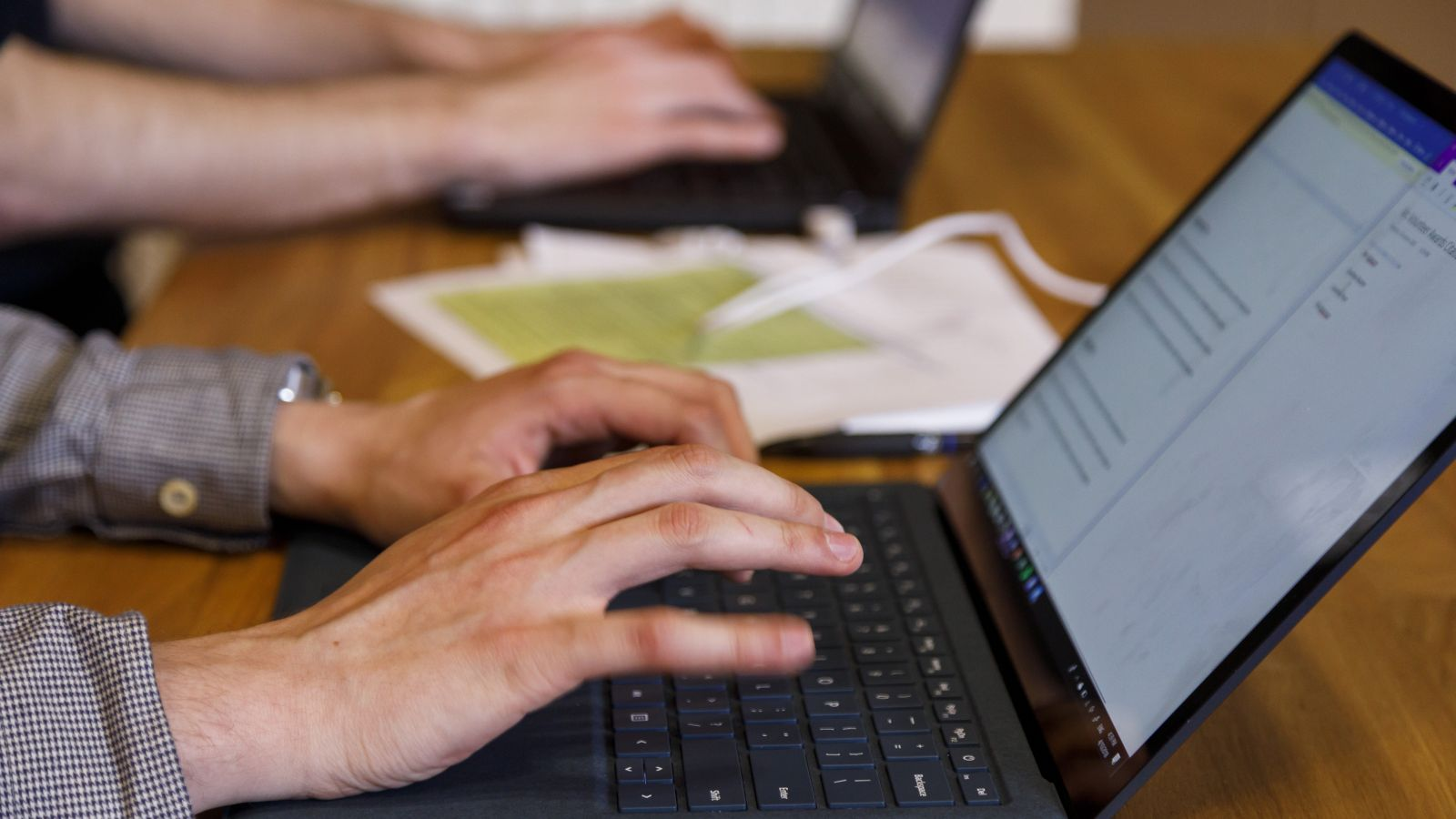 Two people's hands are typing on individual laptops