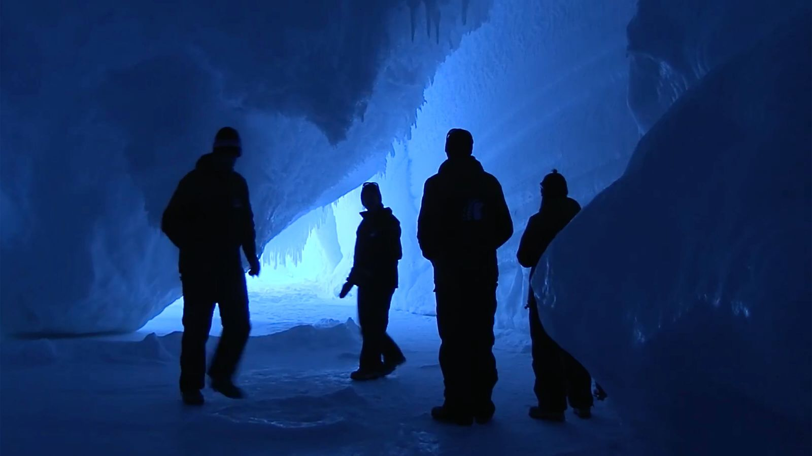 Human silhouettes explore an intensely blue ice cave.