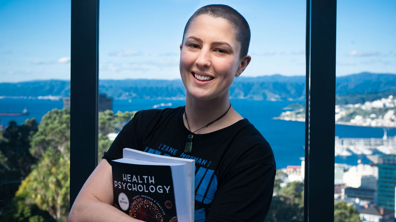A portrait of Carly with the Wellington harbour in the background