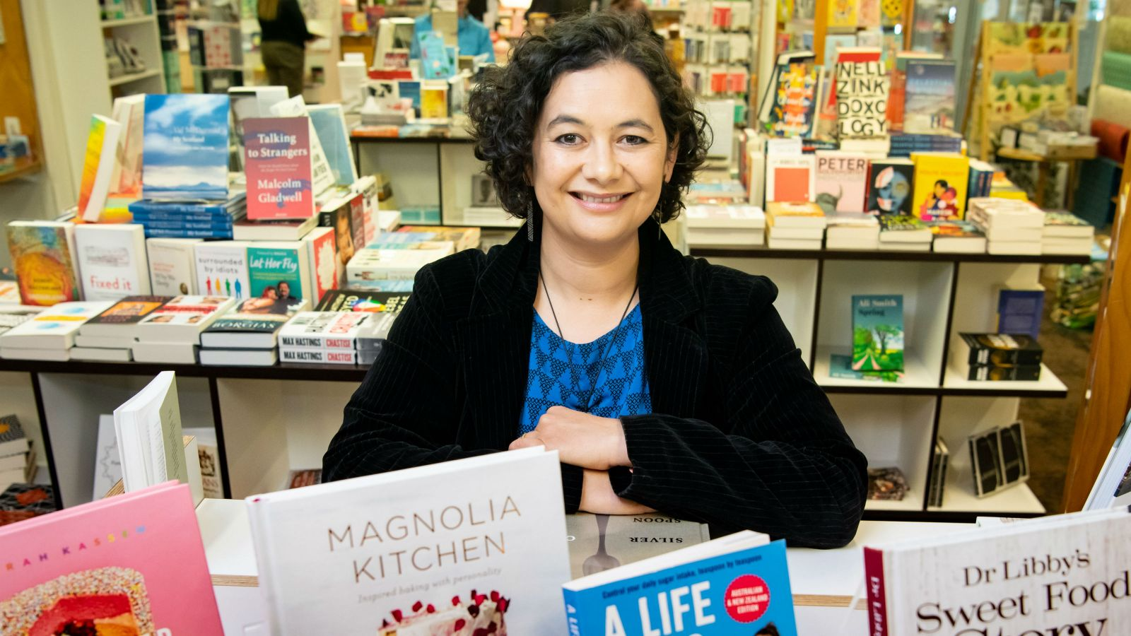Lisa Te Morenga posing for a photo in a bookshop with books about sugar in the foreground