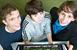 Three students looking at a computer