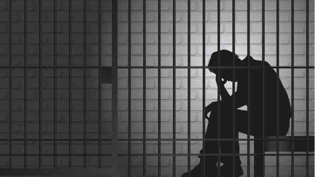 Silhouette of a prisoner behind bars.