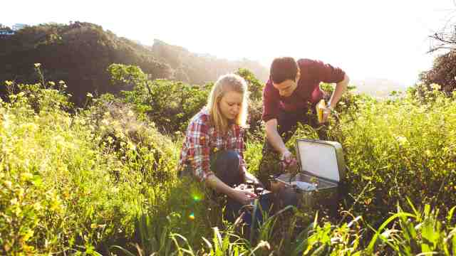 Two PhD students conducting a scientific experiment in a field.