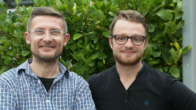 Lecturer Marco Sonzogni and postgraduate student Rory McKenzie stand in front of a leafy green backdrop.