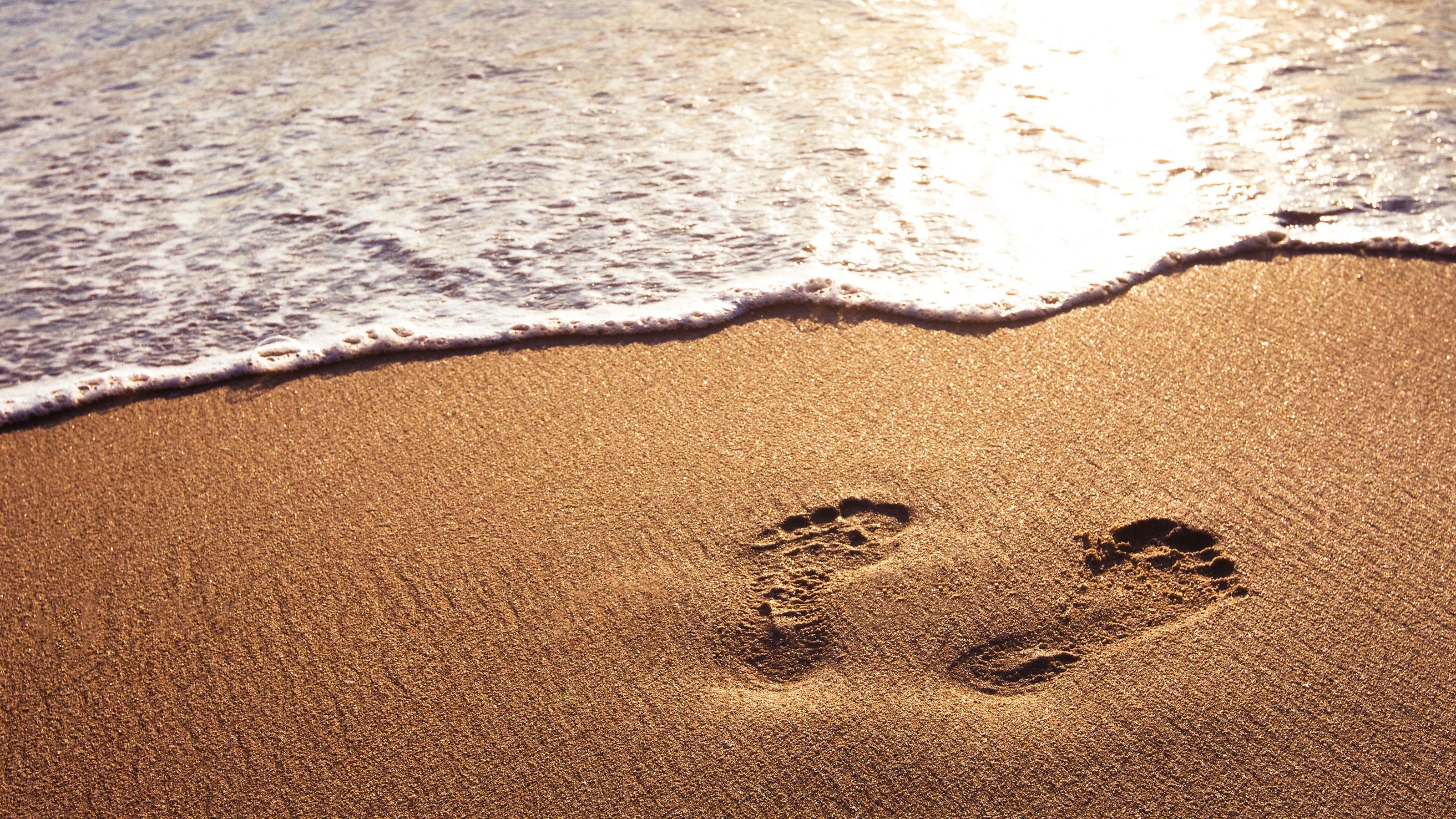 footprints on the sand with wave breaking on shore