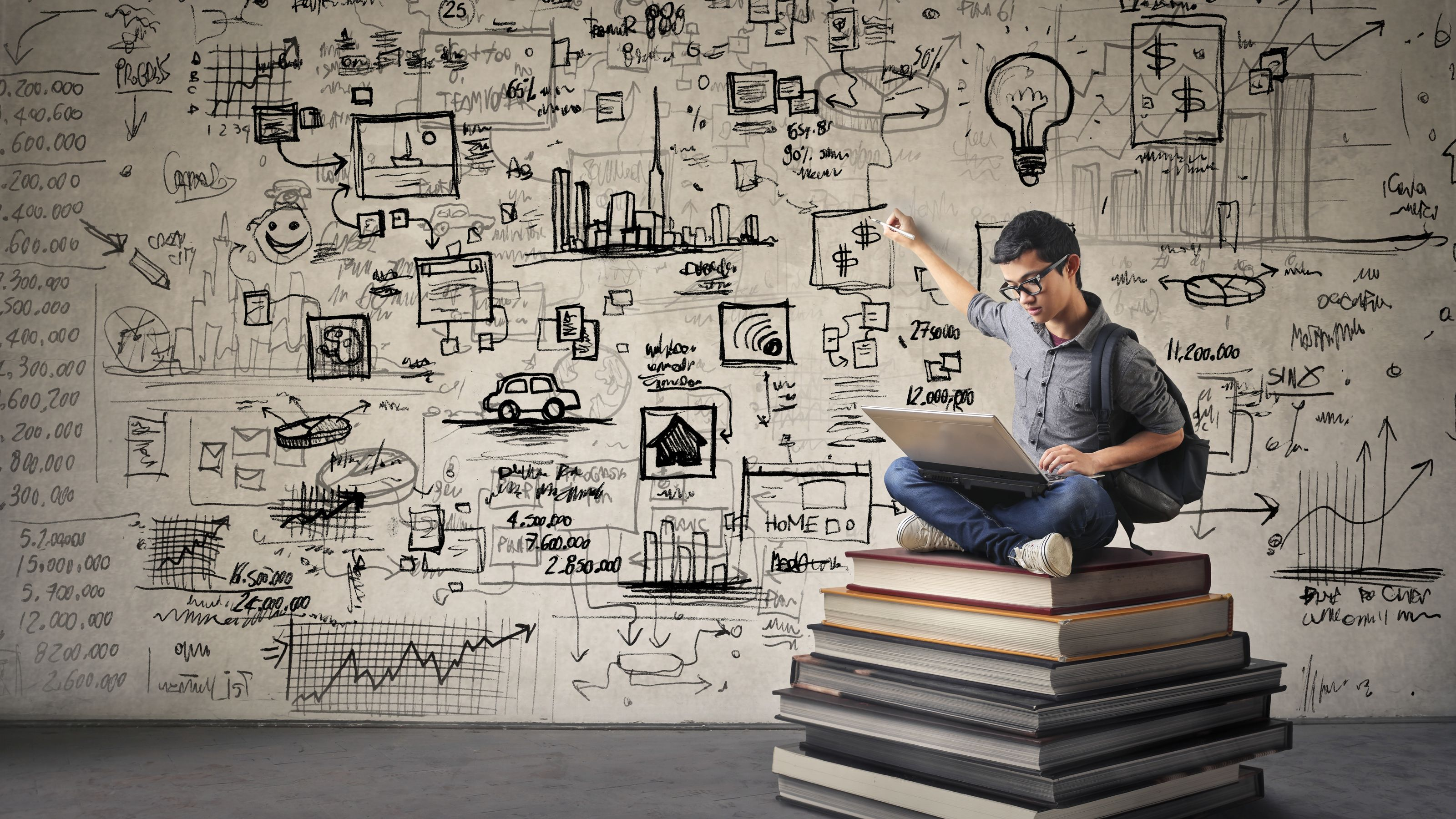 student sitting on top of a pile of academic books with ideas on a whiteboard behind him