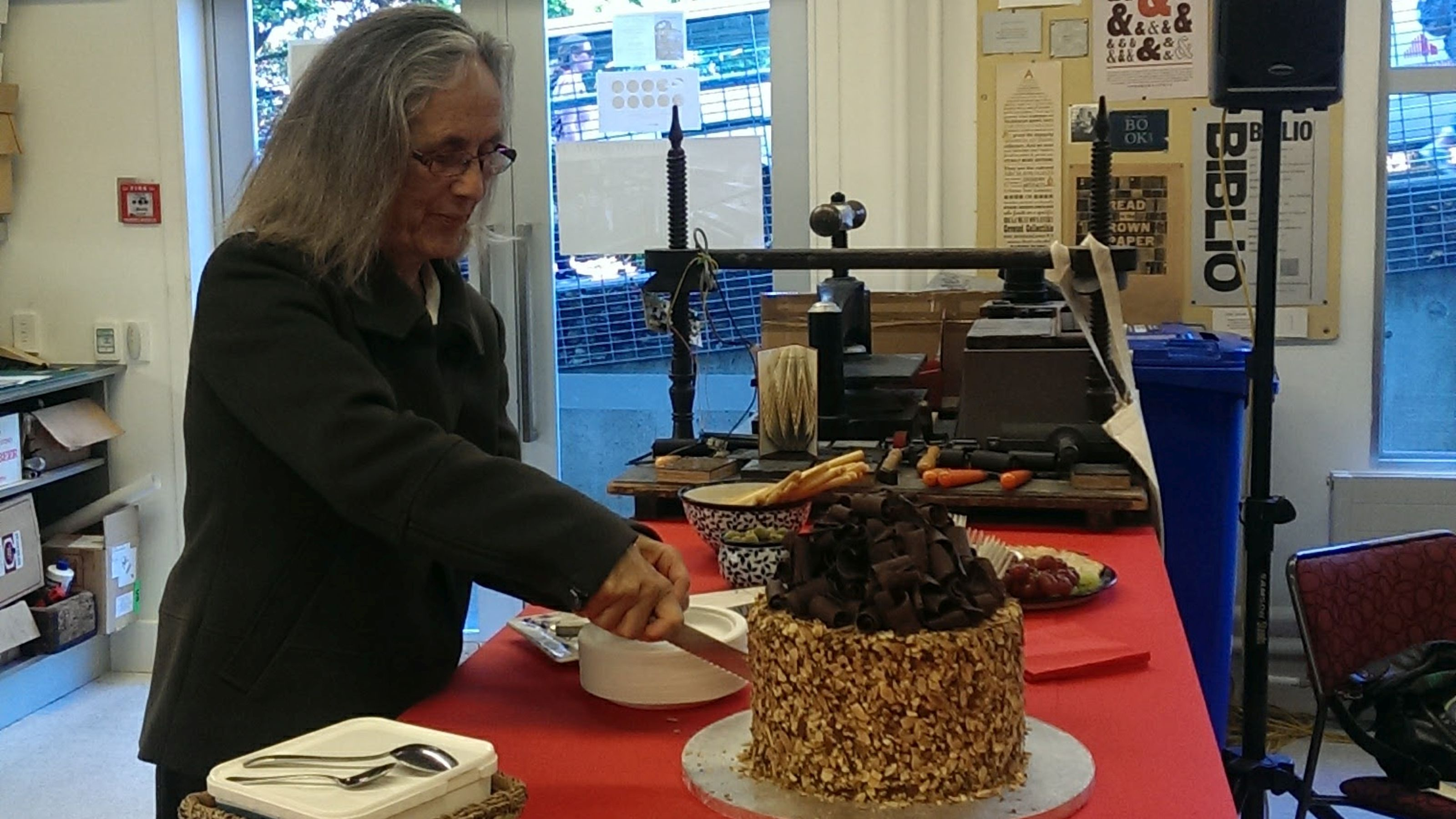 Author Patricia Grace cuts a very elaborate birthday cake topped with chocolate curls.