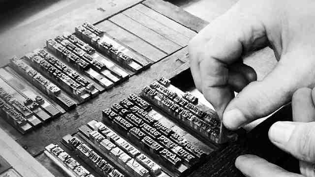 The Printer's hands insert a space into the locked up metal type waiting to be printed.
