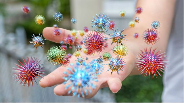 Dozens of colourful spikey spheres orbiting an outstretch human hand.