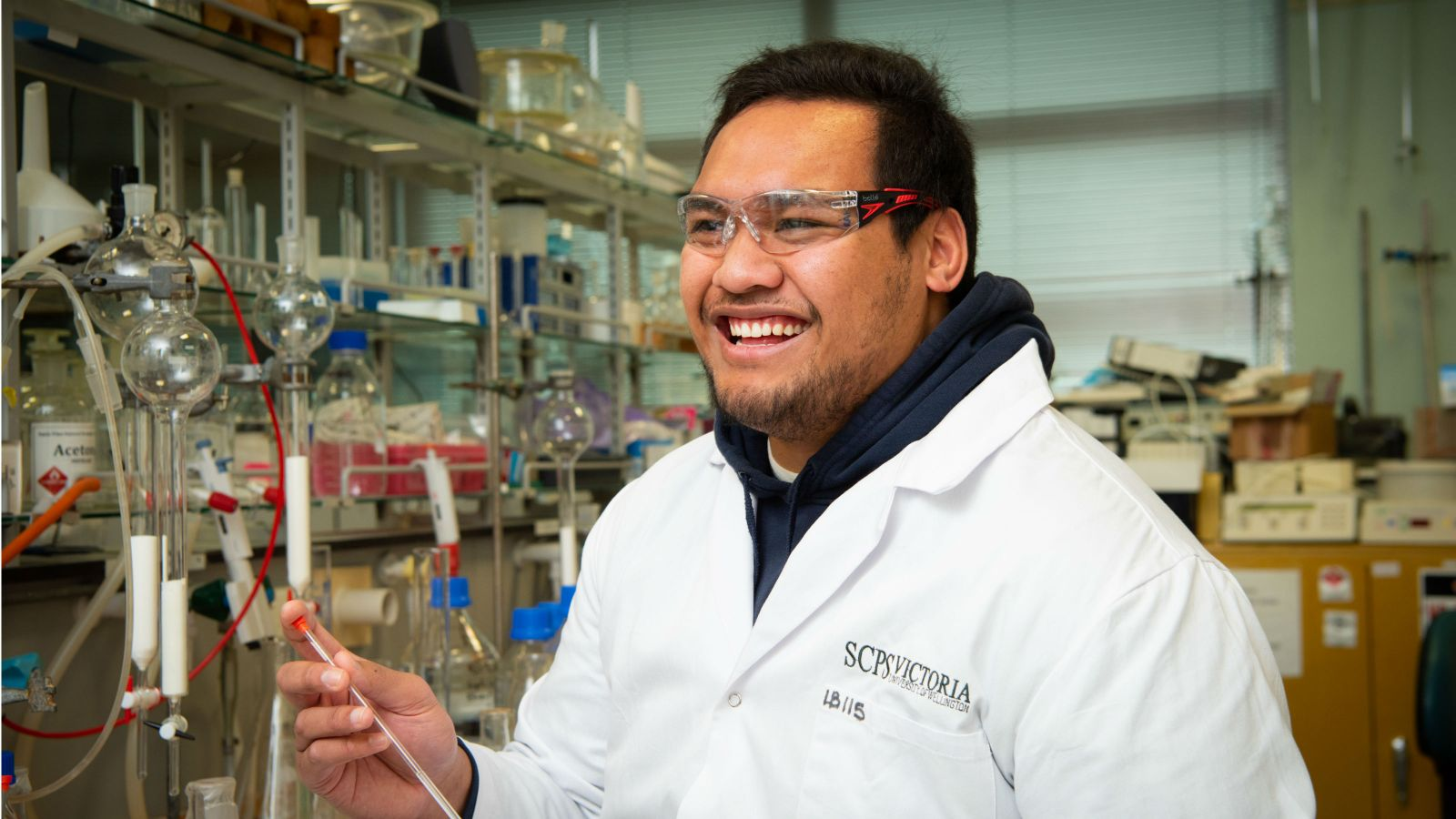 Brettelemani wears a lab coat and sits in a chemistry lab. He is laughing at something off camera and holding equipment.
